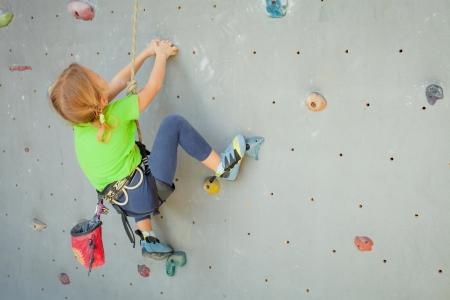 小さな女の子クライミング岩壁 写真素材
