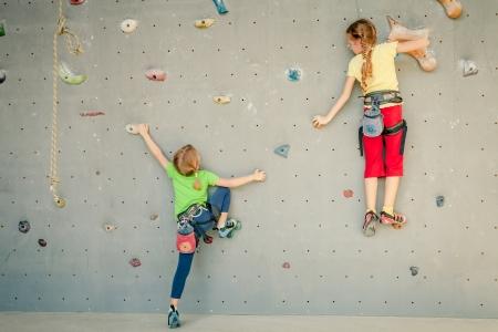 바위 벽을 등반 두 어린 소녀 스톡 콘텐츠
