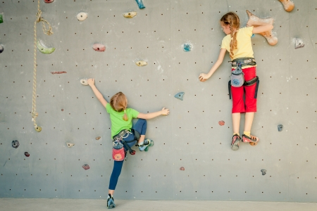 fear child: two little girls climbing a rock wall