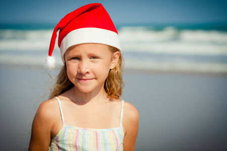 Adorable happy smiling girl in santa hat on beach vacation photo