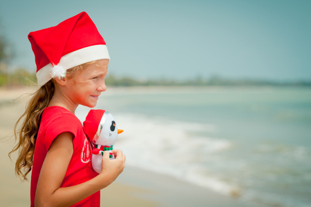 Adorable happy smiling girl in santa hat  hugging toy snowman on beach vacation photo