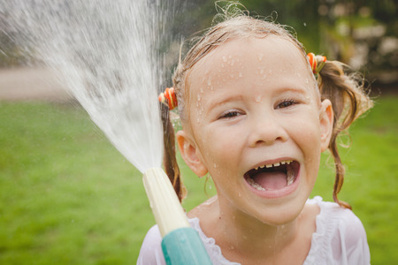 moisten: Happy girl pouring water from a hose
