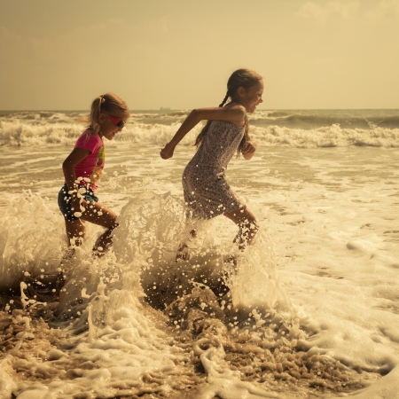 Happy kids running at the beach in the day time photo