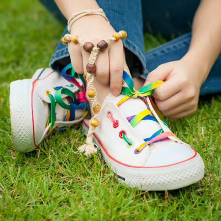 shoelace: white sneakers on girl legs on grass during sunny serene summer day
