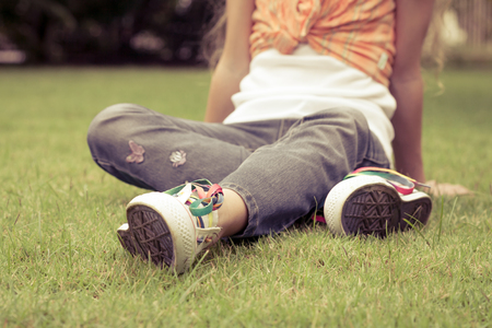 young people fun: white sneakers on girl legs on grass during sunny serene summer day