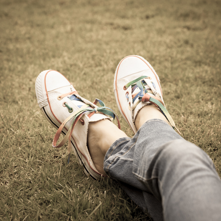 white sneakers on girl legs on grass during sunny serene summer day  photo