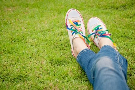 맑은 고요한 여름 하루 동안 잔디에 여자 다리에 흰색 운동화
