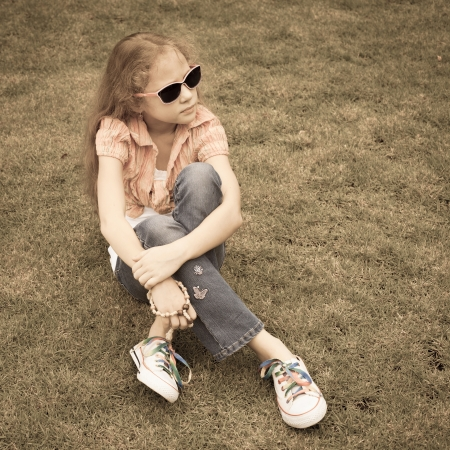 Teen girl in the park sitting on the grass  photo