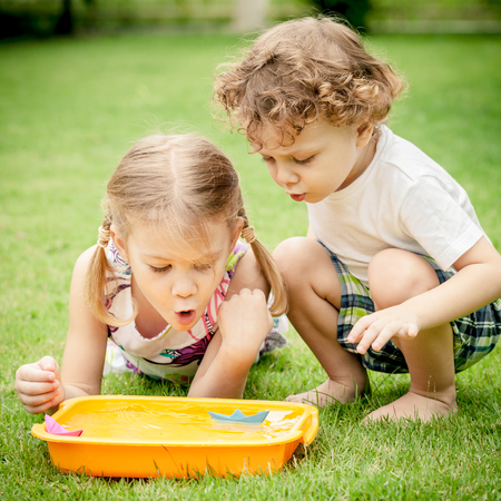 two happy little kids playing in the garden Stock Photo - 24098535