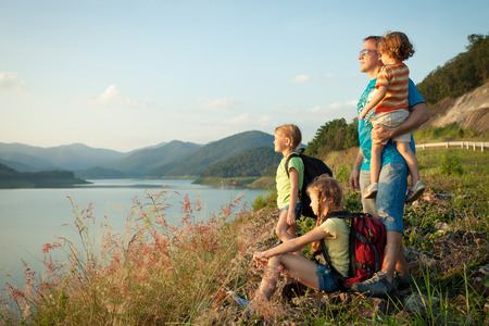 freedom leisure activity: Happy family watching the sunset on the lake
