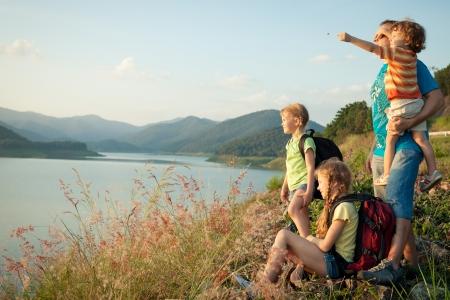 幸せな家族は湖の夕日 写真素材