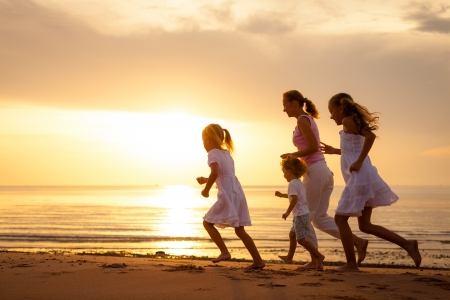 Happy family is running at the beach on the dawn time photo