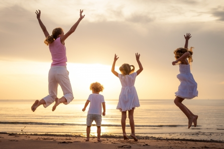 gezonde mensen: Gelukkige mooie familie dansen op het strand aan de dageraad tijd Stockfoto