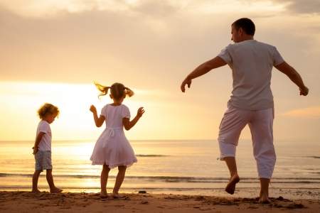 Happy beautiful family dancing on the  beach on the  dawn time  photo