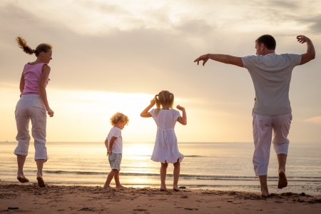 Gelukkige mooie familie dansen op het strand op de dageraad tijd