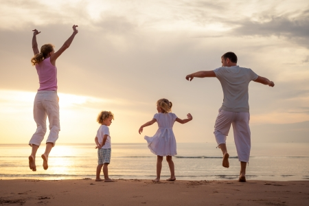 family time: Happy beautiful family dancing on the  beach on the  dawn time  Stock Photo