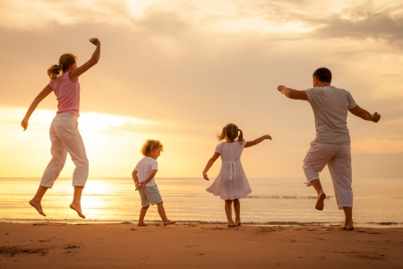 Happy beautiful family dancing on the  beach on the  dawn time  Standard-Bild