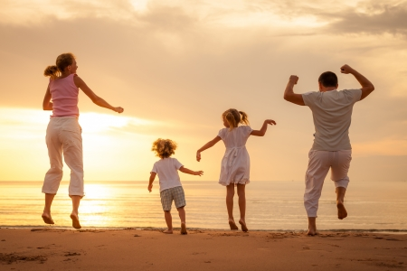 Happy beautiful family dancing on the  beach on the  dawn time  Banco de Imagens