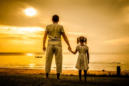 love sad: father and daughter standing at the beach in the dawn time