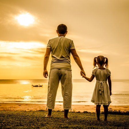vader en dochter die zich op het strand in de dageraad tijd Stockfoto