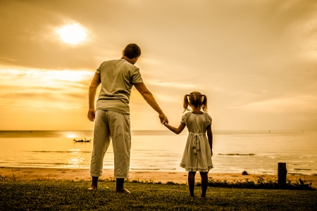 father and daughter standing at the beach in the dawn time photo