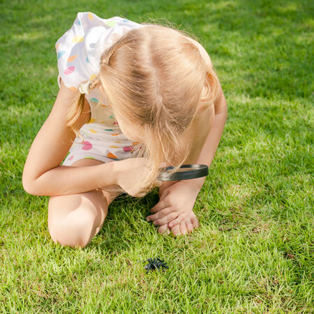 one little girl: one little girl with magnifying glass outdoors in the day time