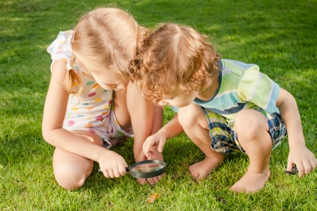 Two little kids  playing with magnifying glass outdoors in the day time Stock Photo