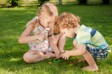 Two little kids  playing with magnifying glass outdoors in the day time photo