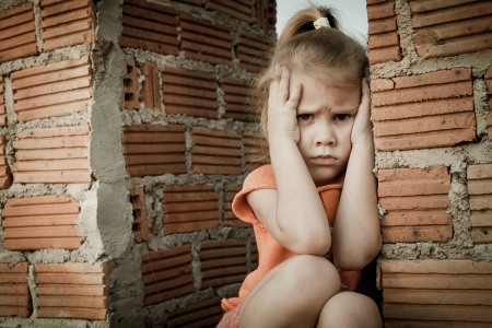 Portrait of sad little girl sitting near brick wall in the day time Stock Photo