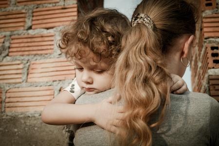 lost child: sad son hugging his mother