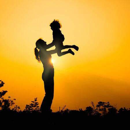 silueta niño: silueta de una madre y su hijo que juegan al aire libre en el fondo del sol