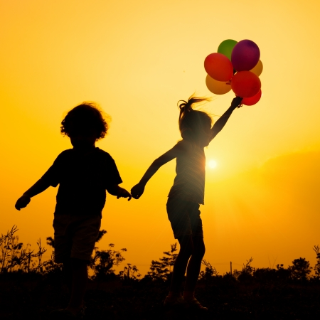 little  girl with balloons jumping on the nature of the evening Stock Photo