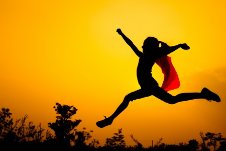 Teen girl in superhero costume jumping in the evening on the nature Stock Photo