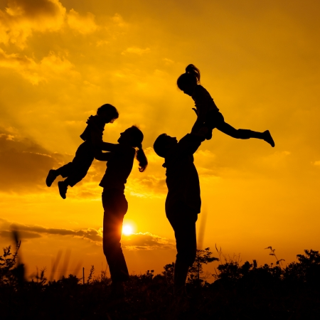 Happy  family playing on the  road in the  sunset time  Evening party on the nature