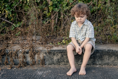 sad little boy sitting near the road Stock Photo