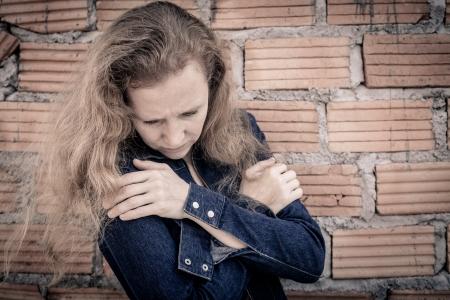 one sad woman sitting  near a brick wall photo