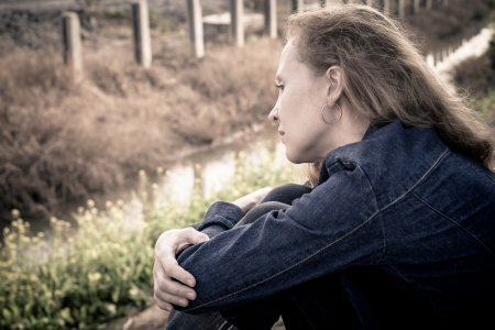 one sad woman sitting  near a river photo