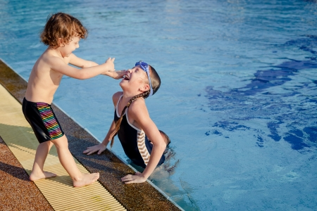 one little girl and little boy playing in the swimming pool photo
