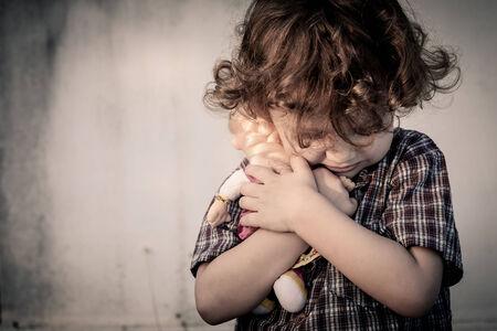 sad boy: sad little boy hugging a doll