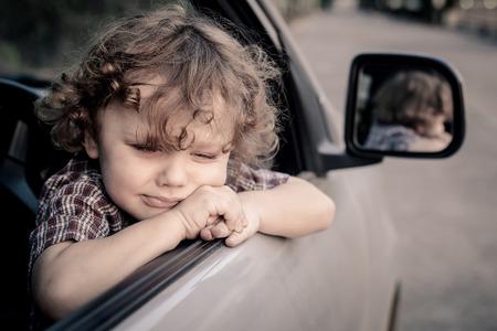 niño llorando: llorando niño sentado en el coche Foto de archivo