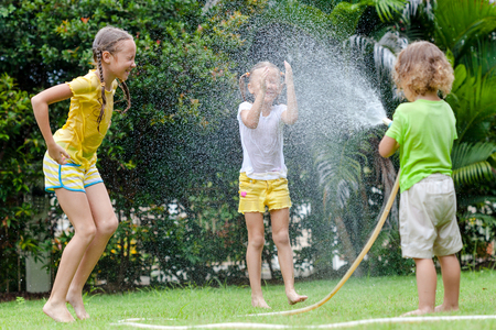 lawn sprinkler: little boy is pouring a water from a hose at his sisters Stock Photo