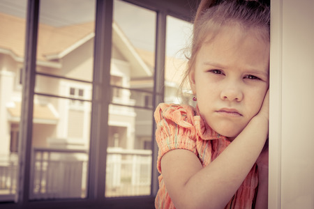 Portrait of sad little girl standing near window in the day time Stock Photo