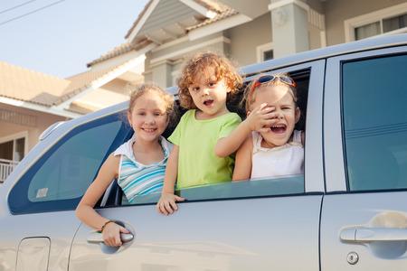 three happy kids sitting in the car photo