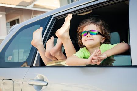 happy little  boy sitting in the car