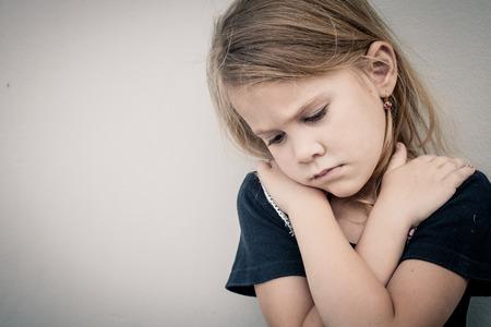 슬픈 어린 소녀는 낮 시간에 벽 근처에 앉아의 초상화 스톡 콘텐츠