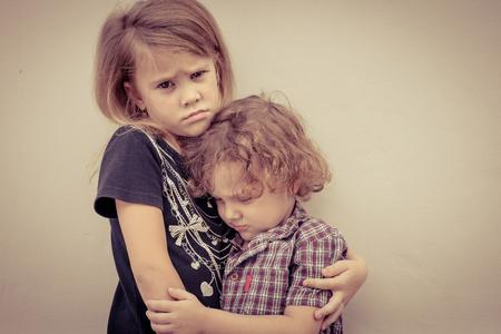 悲しい少女と、一日の時間の壁の近くに立って小さな男の子の肖像画