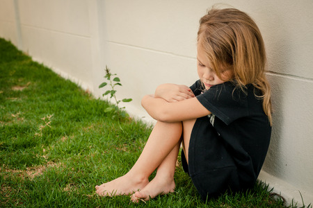 problemas familiares: Retrato de niña triste que se sienta cerca de la pared durante el día