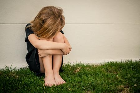 fille triste: Portrait de petite fille triste assis près du mur dans la journée