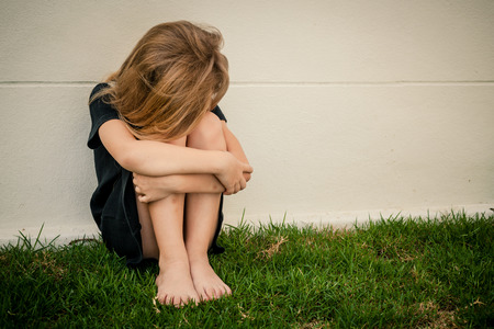 Portrait of sad little girl sitting near  wall in the day time photo