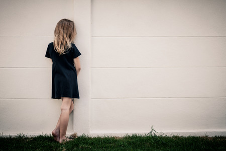 Portrait of sad little girl standing near wall in the day time photo